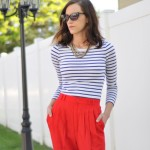 Red pleated trousers and cat eye glasses